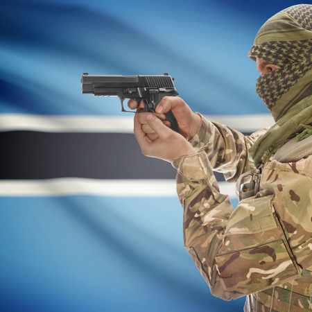 national police agency: Man with gun in hand and national flag on background series - Botswana