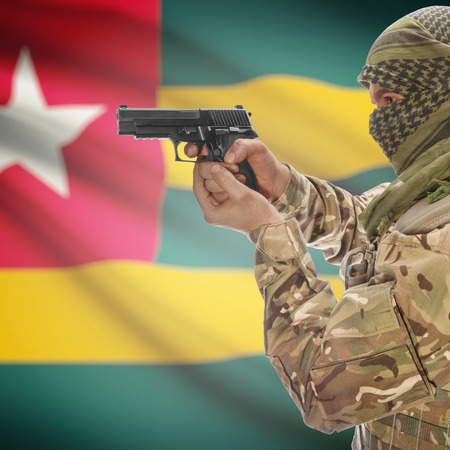 national police agency: Man with gun in hand and national flag on background series - Togo