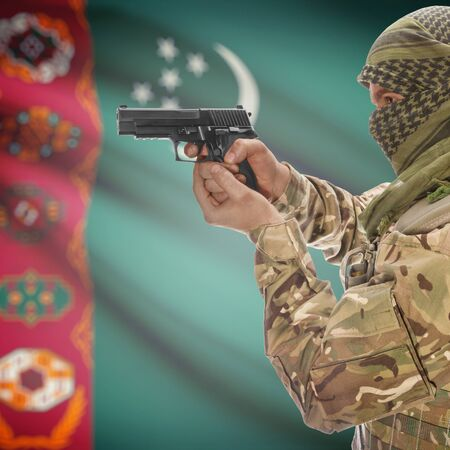 national police agency: Man with gun in hand and national flag on background series - Turkmenistan Stock Photo