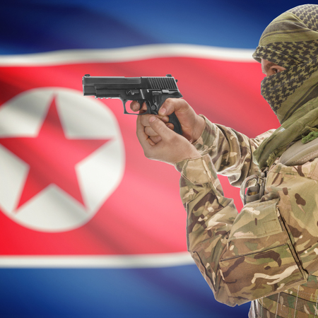 counterterrorism: Man with gun in hand and national flag on background series - North Korea Stock Photo