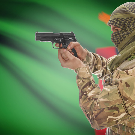 counterterrorism: Man with gun in hand and national flag on background series - Zambia Stock Photo