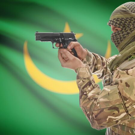anti terrorist: Man with gun in hand and national flag on background series - Mauritania Stock Photo
