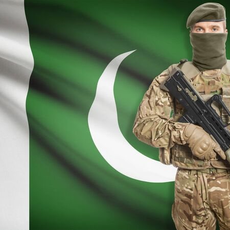 border patrol: Soldier with machine gun and national flag on background series - Pakistan