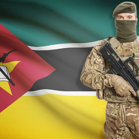 border patrol: Soldier with machine gun and national flag on background series - Mozambique Stock Photo