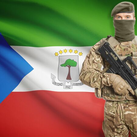 equatorial guinea: Soldier with machine gun and national flag on background series - Equatorial Guinea