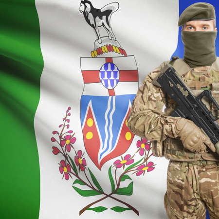 machinegun: Soldier with machine-gun in hands and Canadian province flag on background series - Yukon Stock Photo