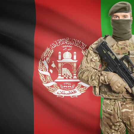 border patrol: Soldier with machine gun and national flag on background series - Afghanistan Stock Photo
