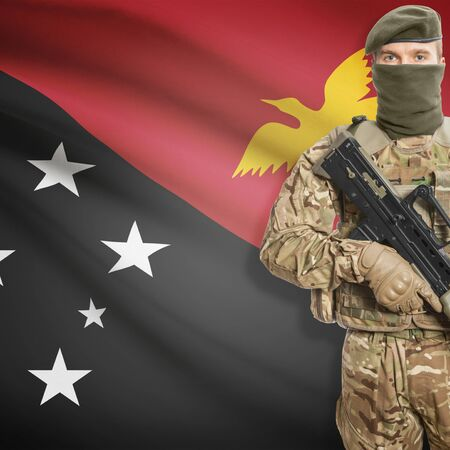 papua new guinea: Soldier with machine gun and national flag on background series - Papua New Guinea Stock Photo