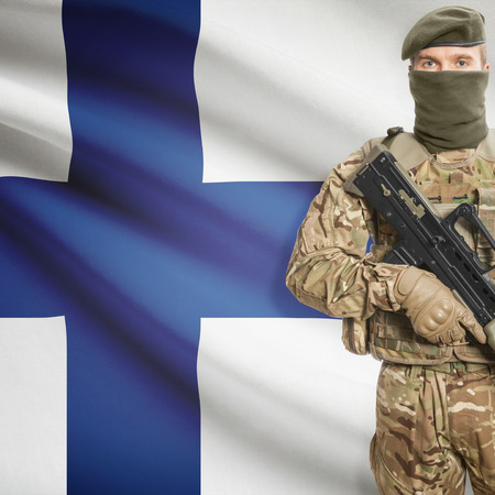 peacemaker: Soldier with machine gun and national flag on background series - Finland Stock Photo