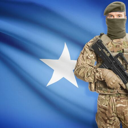 border patrol: Soldier with machine gun and national flag on background series - Somalia Stock Photo