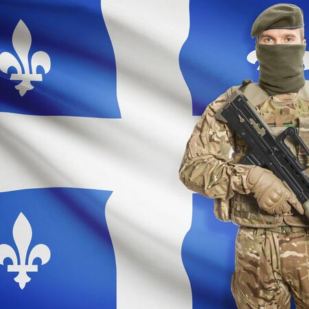 peacemaker: Soldier with machine-gun in hands and Canadian province flag on background series - Quebec Stock Photo