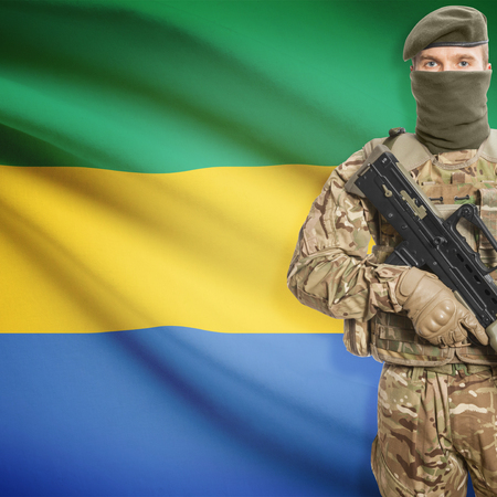 border patrol: Soldier with machine gun and national flag on background series - Gabon Stock Photo