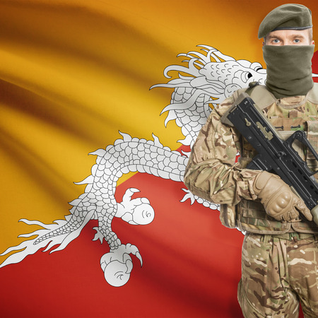 border patrol: Soldier with machine gun and national flag on background series - Bhutan
