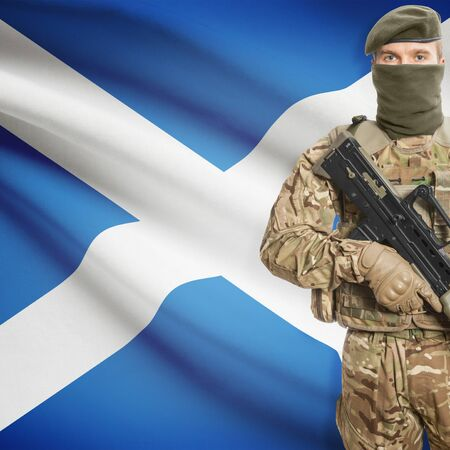 border patrol: Soldier with machine gun and national flag on background series - Scotland Stock Photo