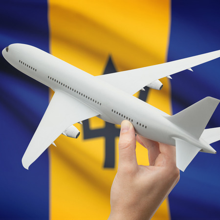 barbadian: Airplane in hand with national flag on background series - Barbados Stock Photo