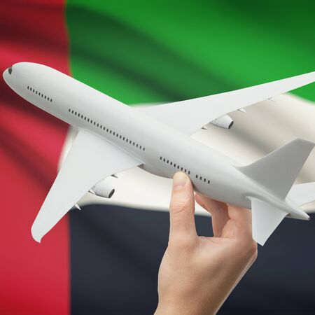 holiday budget: Airplane in hand with national flag on background series - United Arab Emirates