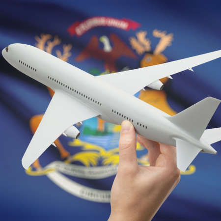 holiday budget: Airplane in hand with local US state flag on background series - Michigan