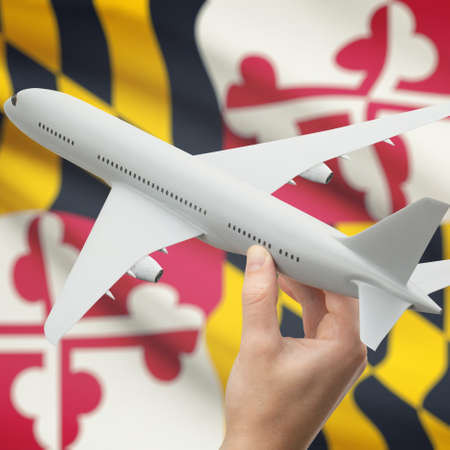 holiday budget: Airplane in hand with local US state flag on background series - Maryland