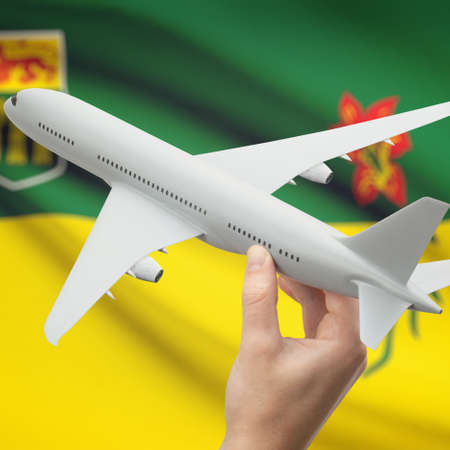 Airplane in hand with Canadian province or territory flag on background series - Saskatchewan Stock Photo