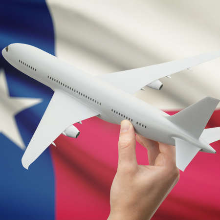 holiday budget: Airplane in hand with local US state flag on background series - Texas