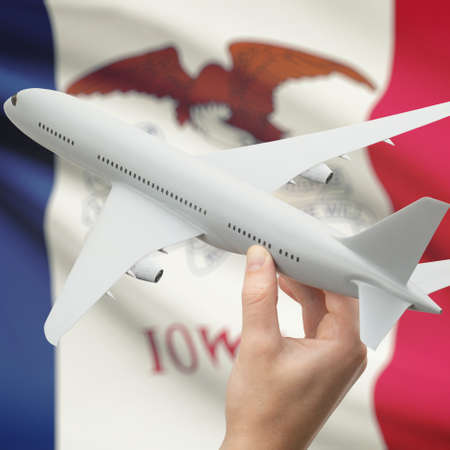 holiday budget: Airplane in hand with local US state flag on background series - Iowa Stock Photo