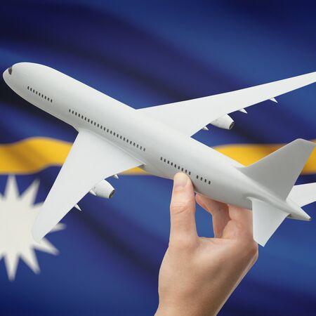 nauru: Airplane in hand with national flag on background series - Nauru