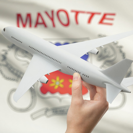 mayotte: Airplane in hand with national flag on background series - Mayotte