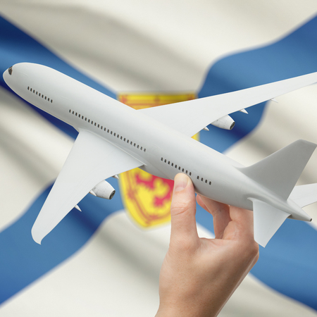 nova scotia: Airplane in hand with Canadian province or territory flag on background series - Nova Scotia Stock Photo