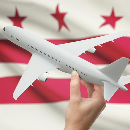 district of columbia: Airplane in hand with local US state flag on background series - District of Columbia