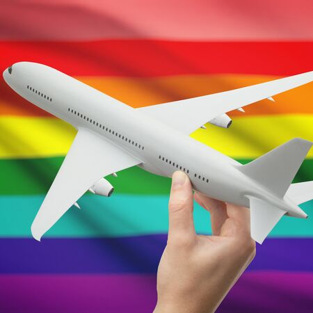 transgender: Airplane in hand withl flag on background series - Lesbian, gay, bisexual and transgender people Stock Photo