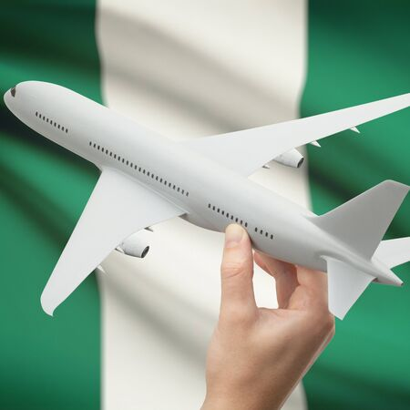 Airplane in hand with national flag on background series - Nigeria
