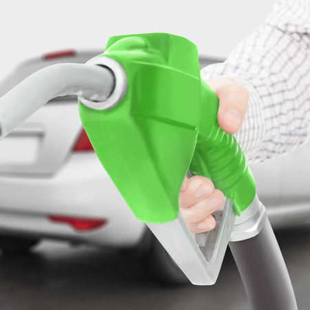 Green color fuel pump gun in hand with car on background - studio shot