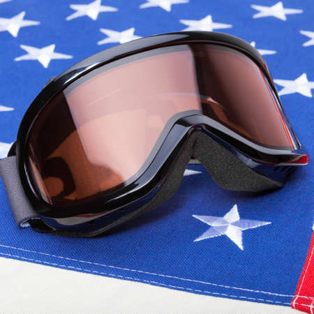 implements: Close up shoot of winter sports implements over US flag - snowboard or ski goggles Stock Photo
