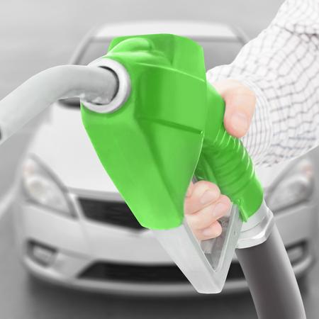 methanol: Fuel pump gun in hand with car on background - studio shot