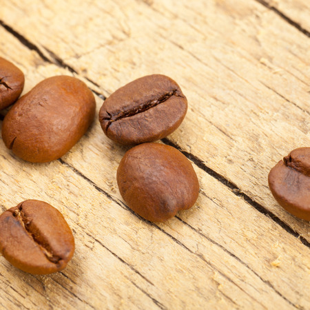 perfectly: Perfectly roasted coffee beans on old wooden table - studio shot