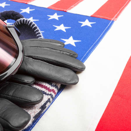 visions of america: Winter sport goggles and gloves over US flag - close up studio shot Stock Photo