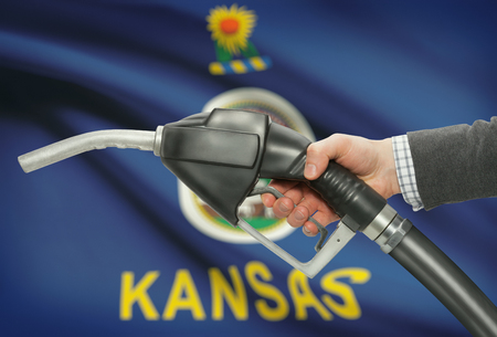 petrochemistry: Fuel pump nozzle in hand with US states flags on background - Kansas