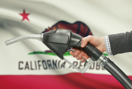 petrochemistry: Fuel pump nozzle in hand with US states flags on background - California