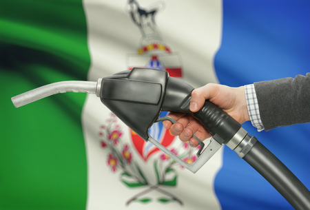 petrochemistry: Fuel pump nozzle in hand with Canadian territories and provinces flags on background - Yukon