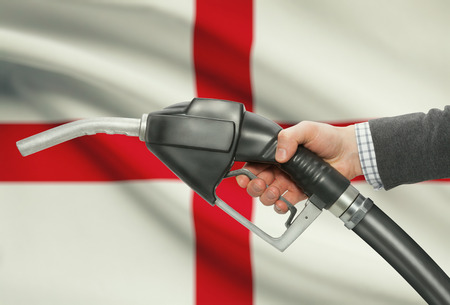 methanol: Fuel pump nozzle in hand with flag on background - England