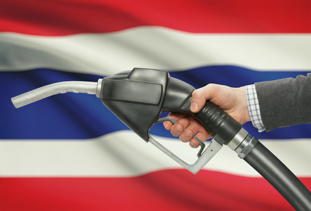 nozzle: Fuel pump nozzle in hand with flag on background - Thailand