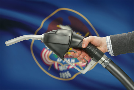 petrochemistry: Fuel pump nozzle in hand with US states flags on background - Utah
