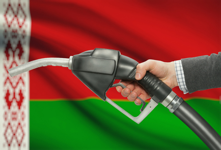 methanol: Fuel pump nozzle in hand with flag on background - Belarus
