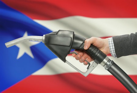 bandera de puerto rico: Fuel pump nozzle in hand with flag on background - Puerto Rico