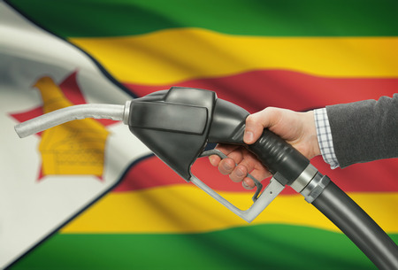 petrochemistry: Fuel pump nozzle in hand with flag on background - Zimbabwe
