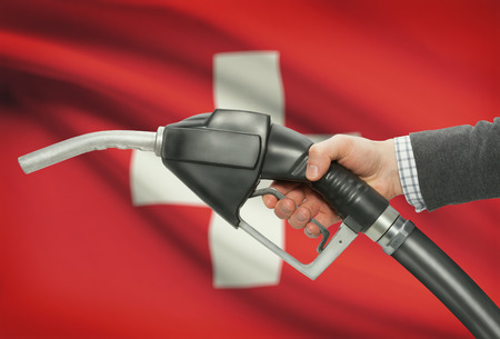petrochemistry: Fuel pump nozzle in hand with flag on background - Switzerland
