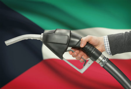 Fuel pump nozzle in hand with flag on background - Kuwait