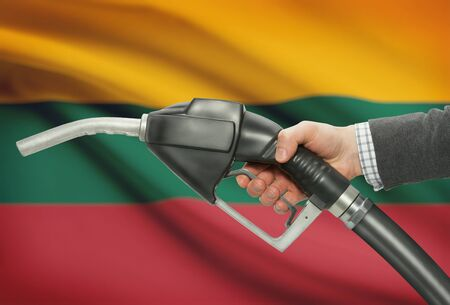 petrochemistry: Fuel pump nozzle in hand with flag on background - Lithuania