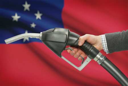 Fuel pump nozzle in hand with flag on background - Samoa