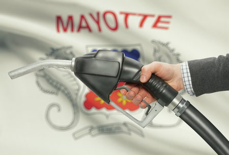 mayotte: Fuel pump nozzle in hand with flag on background - Mayotte Stock Photo